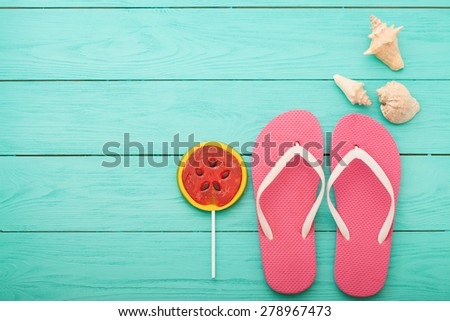 Flip-flops near candy and shells on blue wooden background - stock photo