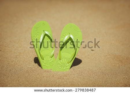flip flops on a sandy beach - stock photo
