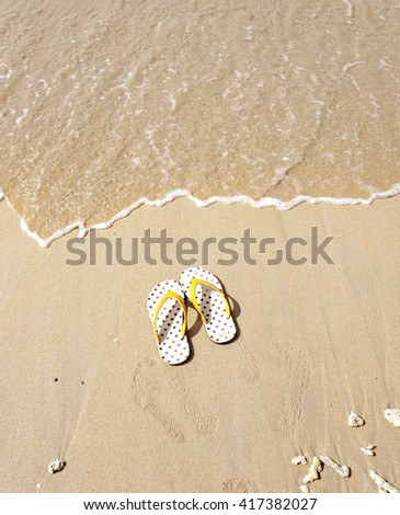 Flip flops on a sandy ocean beach - stock photo