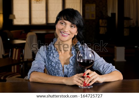 Flirtatious young woman drinking at a bar turning to give a big inviting smile to another customer as she holds a large glass of red wine - stock photo
