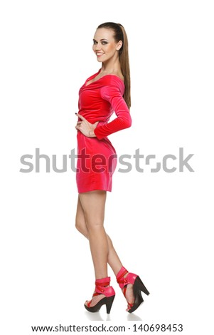 Flirtatious young woman in pink dress standing in full length against white background - stock photo