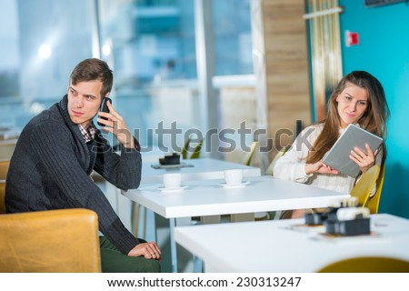 Flirting couple in cafe using digital tablet and telephone, selective focus - stock photo