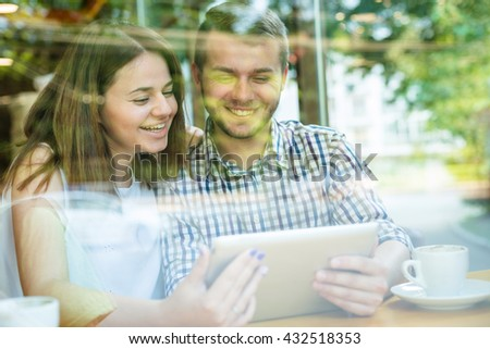 Flirting couple in cafe using digital tablet. looking through window - stock photo