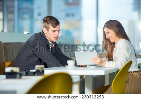 Flirting couple in cafe using digital tablet, selective focus - stock photo