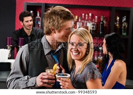 Flirting young happy friends enjoy drinks at cocktail bar - stock photo