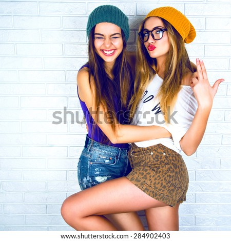 Flirty beauty. Portrait of beautiful young  two attractive young women making selfies together. Dressed in shorts and a bright cap on a white background. - stock photo