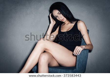 Flirty in chair. Beautiful young African woman in black swimsuit looking at camera and keeping legs crossed at knees while sitting in chair against grey background - stock photo