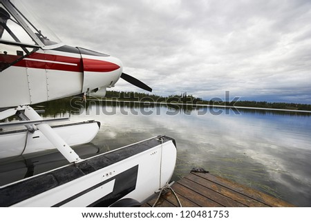 Float plane tied up to wooden dock at lake - stock photo