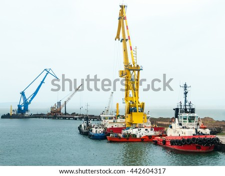Floating cranes on the construction of the bridge - stock photo