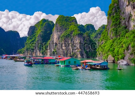 Floating fishing village near rock islands in Halong Bay, Vietnam, Southeast Asia. UNESCO World Heritage Site. - stock photo