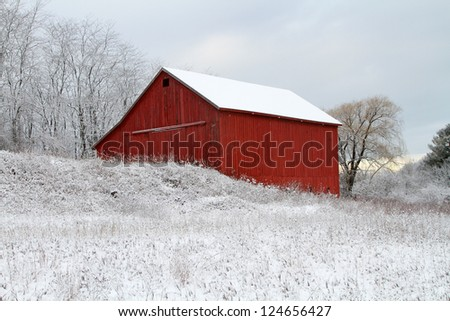 Flocked -- A historic red barn sits on top of a hill after a fresh snowfall in Pentwater, Michigan. - stock photo