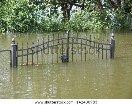 floded fence after heavy rains - stock photo