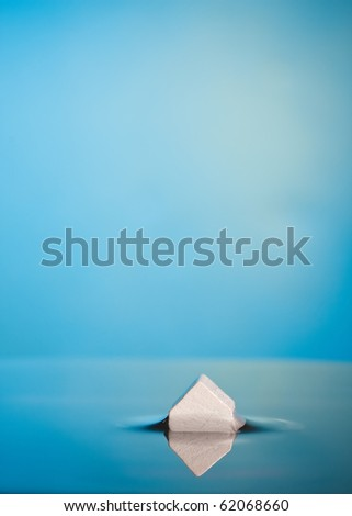 Flood or foreclosure Concept. Abstract Macro of a little white house in blue water  with ample copy-space. - stock photo