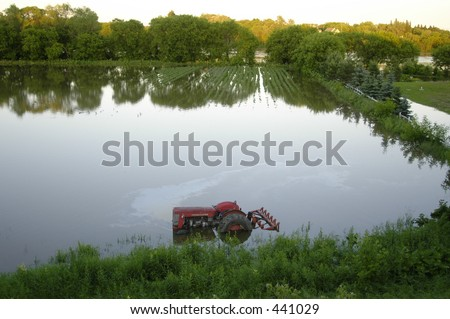 Flooded farm field and tractor - stock photo