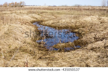 Flooded farm land corn field with remains after harvesting due to heavy rain causing a puddle and wet land on a sunny spring day with a blue cloudy sky - stock photo