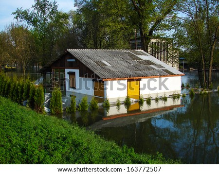 Flooded house on a river bank - stock photo