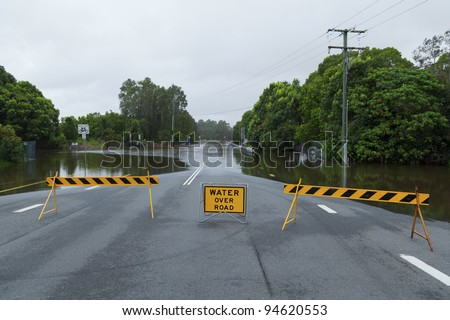 Flooded suburban road with road block in Australia - stock photo
