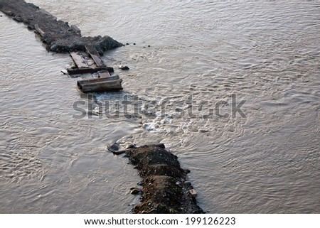 Flooding:overflow through an old ruined levee - stock photo