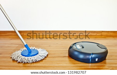 floor washing robot VS traditional mop on laminate floor - stock photo