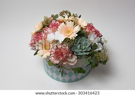 Floral arrangement in round box on white background - stock photo