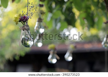 Floral decor in light bulbs hung around for the wedding ceremony - stock photo