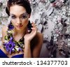 floral face art with anemone in jewelry, sensual young brunette woman - stock photo