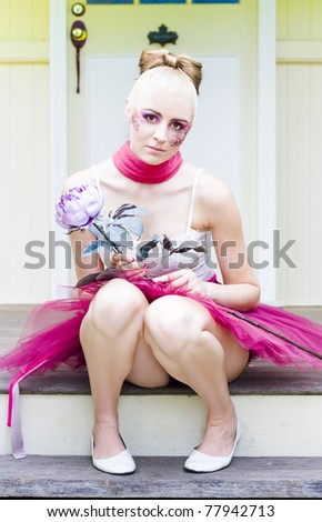 Floral Woman Sits At The Top Of The Stairs Near The Front Door Of A Home Or House Holding A Large Purple Flower While Wearing Purple Floral Design Makeup - stock photo