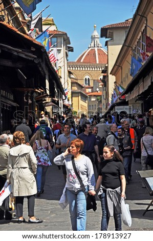 FLORENCE, ITALY - APRIL 20, 2011: Spring tourists on the Ponte Vecchio bridge viewing the gold and silver jewelry shops in the week before Easter. The dome of the Duomo is in the background.  - stock photo