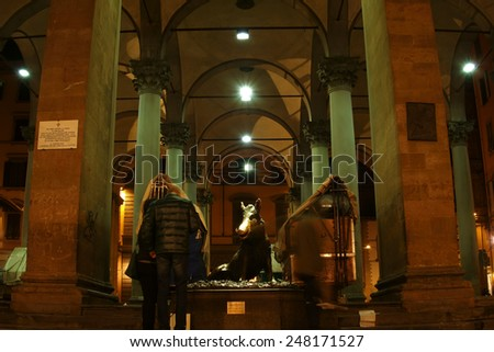 FLORENCE, ITALY - JANUARY 18, 2015:  the famous Porcellino bronze statue of a wild boar, symbol of Tuscany and tourist attraction in Piazza del Mercato Nuovo at night - stock photo
