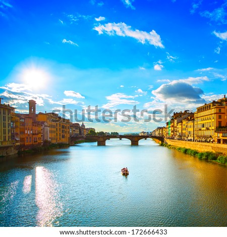 Florence or Firenze, Ponte Santa Trinita medieval Bridge landmark on Arno river and a boat, sunset landscape. Tuscany, Italy. - stock photo