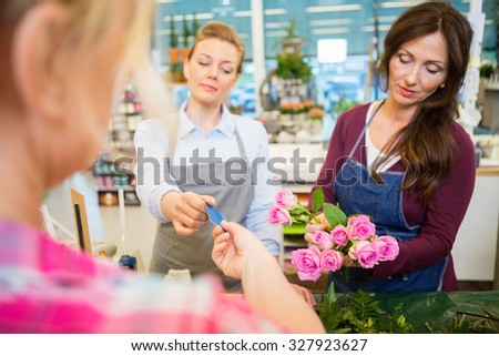 Florist accepting credit card from customer while colleague making rose bouquet at shop - stock photo