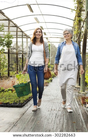 Florist and customer walking together in a greenhouse - stock photo