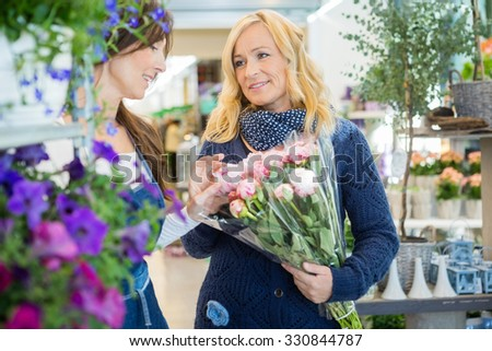 Florist assisting female customer in buying flower bouquet at store - stock photo