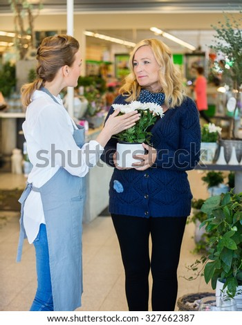 Florist assisting female customer in buying flower plants at store - stock photo