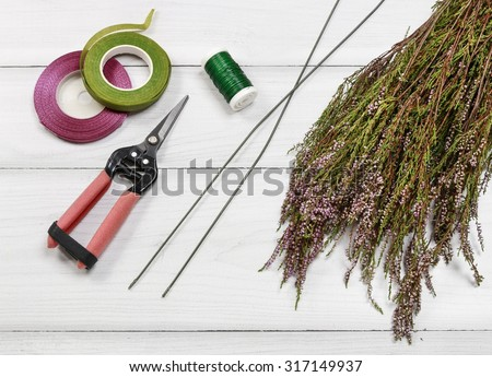 Florist at work: steps of making heather (erica) door wreath in heart shape, step by step, tutorial.  - stock photo