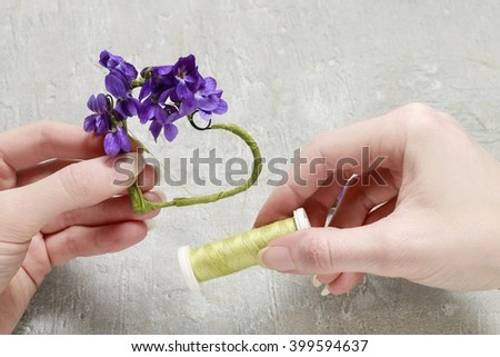 Florist at work: steps of making viola odorata (violets) wreath in heart shape, step by step, tutorial. - stock photo