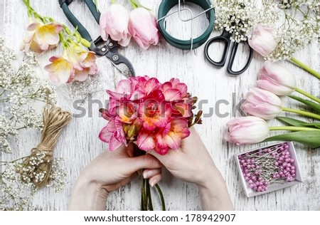 Florist at work. Woman making bouquet of spring freesia flowers - stock photo