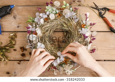Florist at work: woman making door wreath with autumn plants and flowers - stock photo