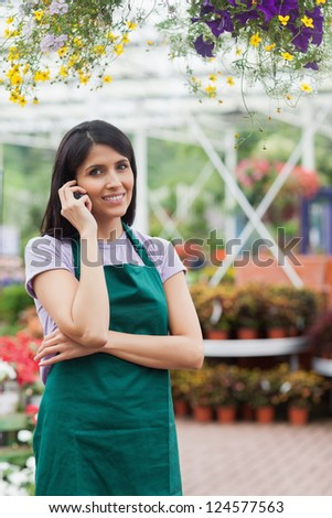 Florist doing a phone call while smiling and standing in the garden center - stock photo