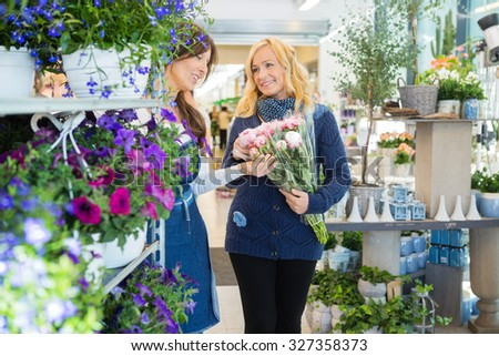 Florist guiding female customer in buying flower bouquet at store - stock photo
