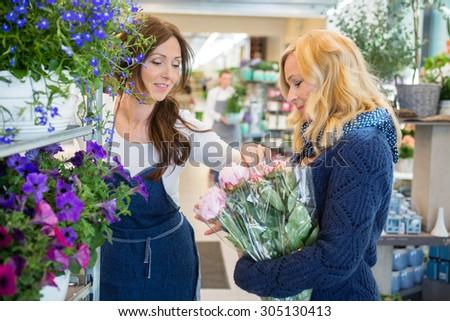 Florist guiding female customer in buying flowers at store - stock photo