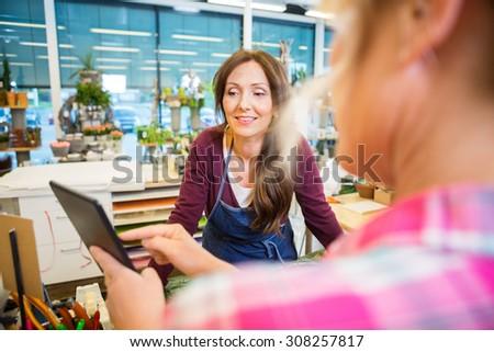 Florist looking at female customer using digital tablet in flower shop - stock photo