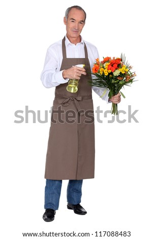 Florist spraying a bouquet of flowers - stock photo