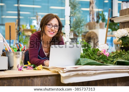 Florist Using Laptop At Counter In Flower Shop - stock photo
