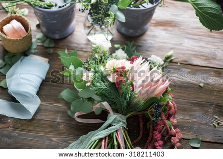 Florist workplace: flowers and accessories on a vintage wooden table. soft focus - stock photo