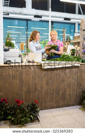 Florists making bouquet at counter in flower shop - stock photo