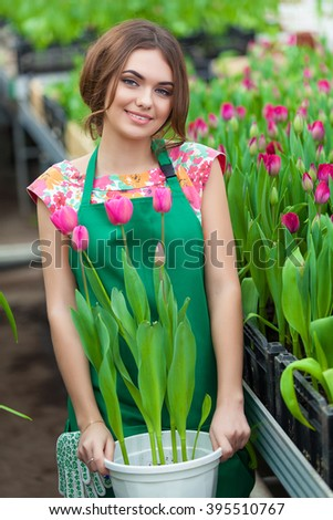 Florists woman working with flowers in a greenhouse. Springtime, lots of tulips - stock photo