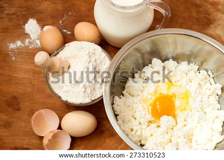 flour, cottage cheese in bowl and milk in a jug. eggs. products for making cheesecakes on a wooden chopping board - stock photo