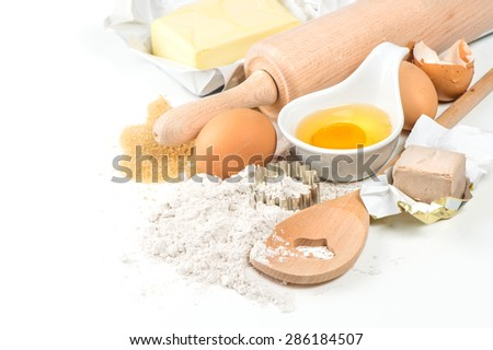 Flour, eggs, yeast, sugar, butter. Wooden kitchen utensils rolling pin and spatula. Food background. - stock photo