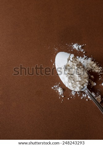 flour for baking in old vintage spoon and egg put on brown paper background - stock photo